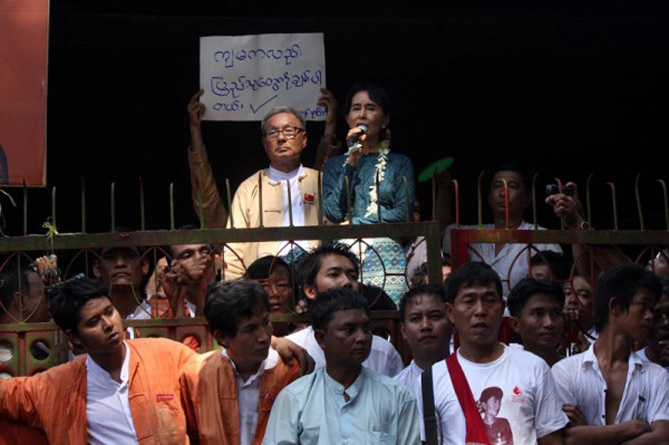 Aung_San_Suu_Kyi_speaking_to_supporters_at_National_League_for_Democracy_NLD_headquarter-1-600x399