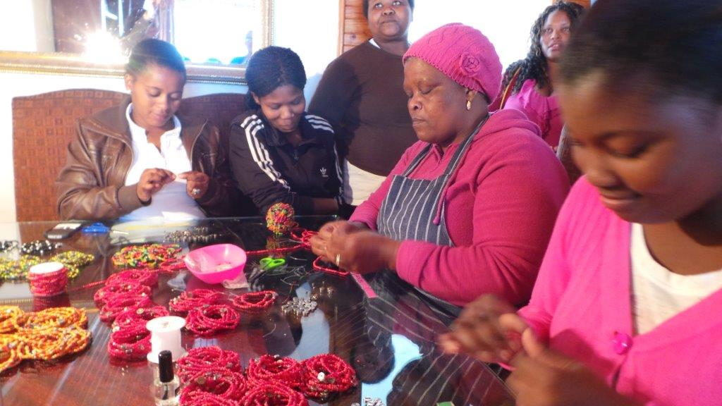 South African women creating the ONE and (RED) bracelets