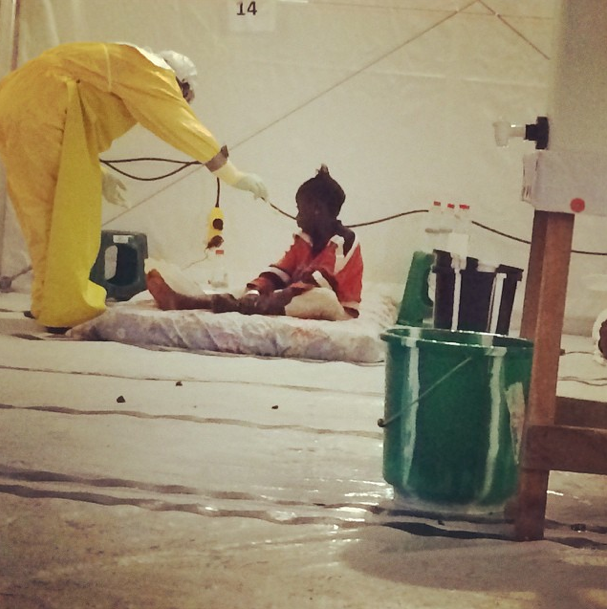 """A little girl all alone at an Ebola treatment unit. A worker feeds her."""