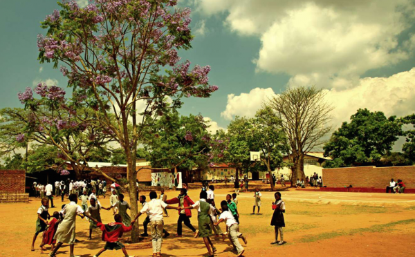 Students gather around the jacaranda tree at the school. (Photo credit: Jacaranda Foundation)