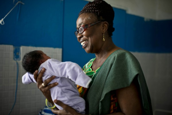 Marion Subah, Jhpiego's Medical Education and Training Advisor in Liberia, holds a newborn baby in the newly built maternity wing of the public hospital in Buchanan, Liberia. (Photo credit: Jhpiego/Kate Holt)