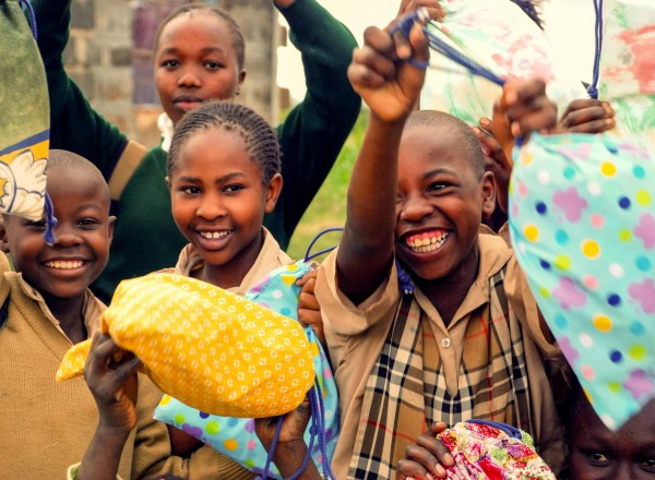Girls in Kenya hold up their Days for Girls Kits. (Photo credit: Days for Girls)