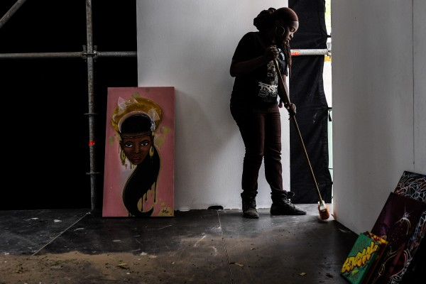 Dakar, Senegal (April 9) - Dieynaba Sidibe, Senegal's first female graffiti artist, sweeps an open gallery space at the Douta Seck Cultural House in Dakar, Senegal to help prepare for the official opening of Festigraff, a 10-day international graffiti festival held each year in the Senegal capital.
