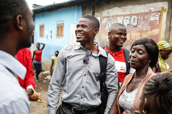 Yusuf Kabba (centre) talks with Ebola survivors in Freetown's Magazine Wharf—one of the city's largest slums where the disease hit families hard. Yusuf is President of the Sierra Leone Association of Ebola Survivors (SLAES). (Photo credit: Simon Davis/DFID)