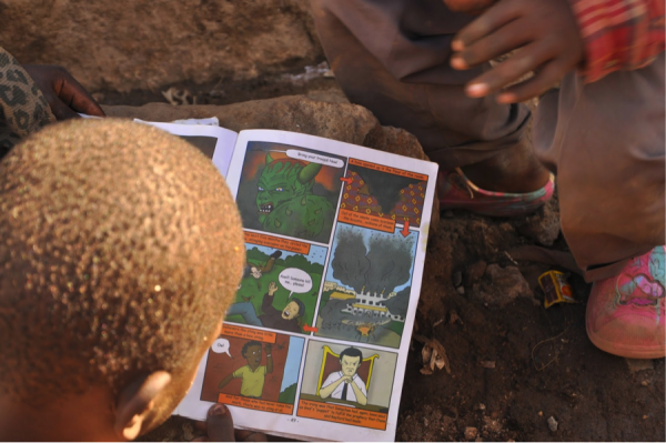 A young boy reading a comic in Mathare. (Photo by Joyce Aidi.)