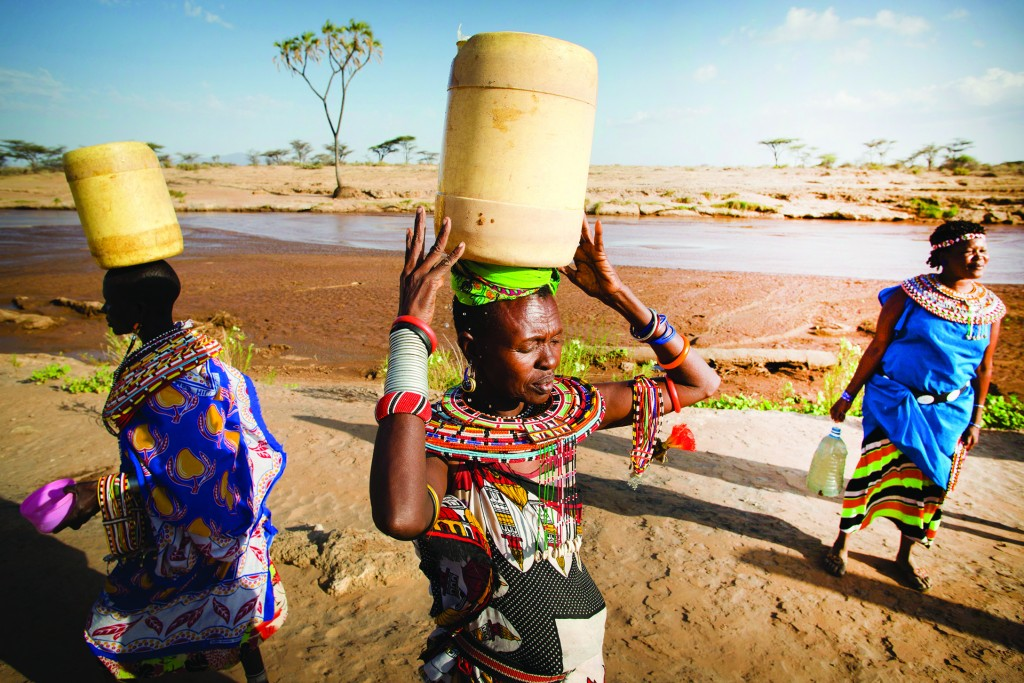 Women walk back to the Umoja village after collecting water from a nearby river, Samburu, Kenya on February 19, 2015.