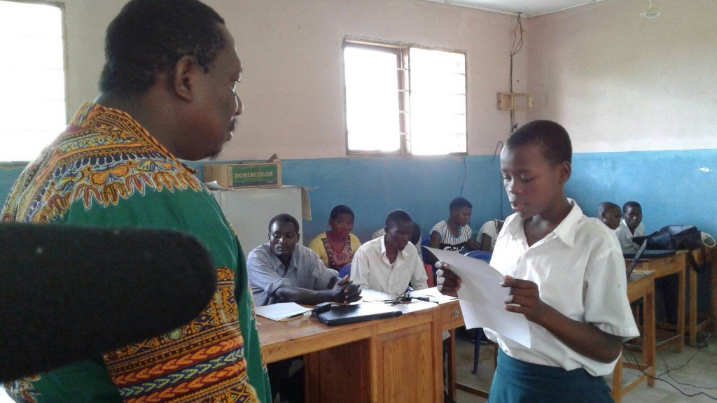 Eva Tolage, right, reads her letter to the Tanzanian government to her District Commissioner. (Photo credit: Restless Development)